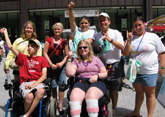 2007 picture of KASA Task Force. Task Force members are at the Disability Pride Parade and are standing as a group with fists raised or with I love you ASL sign